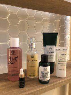 Produtos de beleza e cuidado facial são expostos em bancada no banheiro.